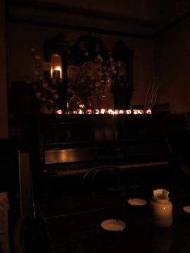 座ったテーブルの横にピアノ。その上の花器にコットン