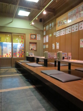 店内、小上がりと入口。向かって左側にテーブル席が並ぶ