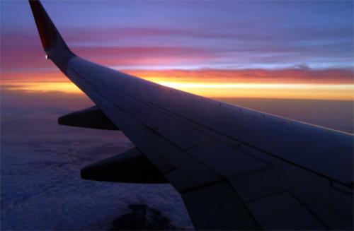 窓から眼下に見下ろす北アルプス連峰と夕焼け空