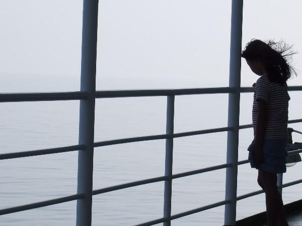 シルエット デッキで海を眺める少女